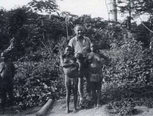 Alan Cooper (East 1926) with pygmies in the Congo. Cooper, a failed Kenyan coffee planter and three associates set out in April 1955 from Nairobi in a Morris Traveller to drive across Africa, through the Sahara Desert and Europe to London.  The poorly planned expedition was to end in failure and his death
